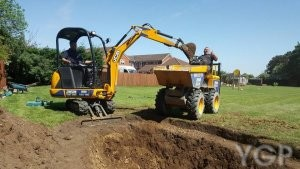 image of a digger next to pond being built